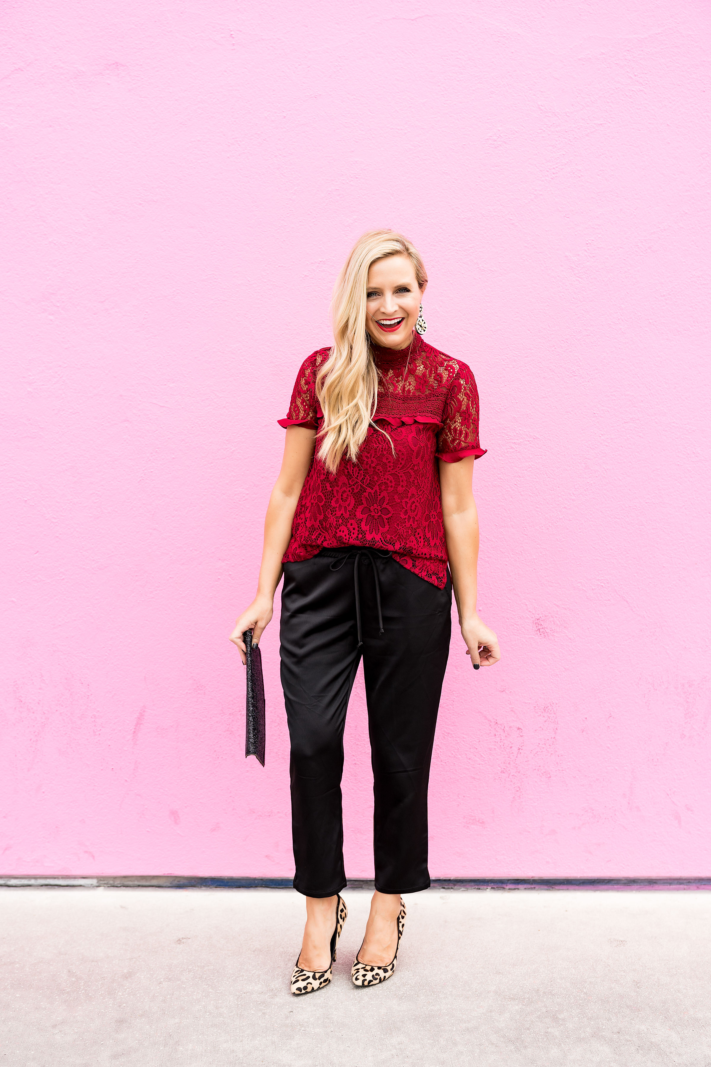 Top Houston fashion blogger, Fancy Ashley, features 7 Holiday Outfits perfect for the season: image of a woman wearing red lace top, black jogger pants, Kate Spade earrings, glitter clutch and sam Edelman leopard pumps all available at Nordstrom