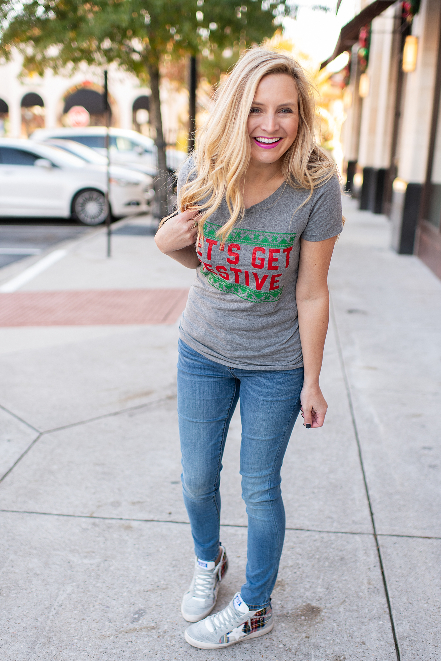 Fancy Ashley x Social Threads collection featured by top Houston fashion blogger, Fancy Ashley: image of a woman wearing a Social Threads festive graphic tee, Social Threads skinny jeans and Golden Goose sneakers