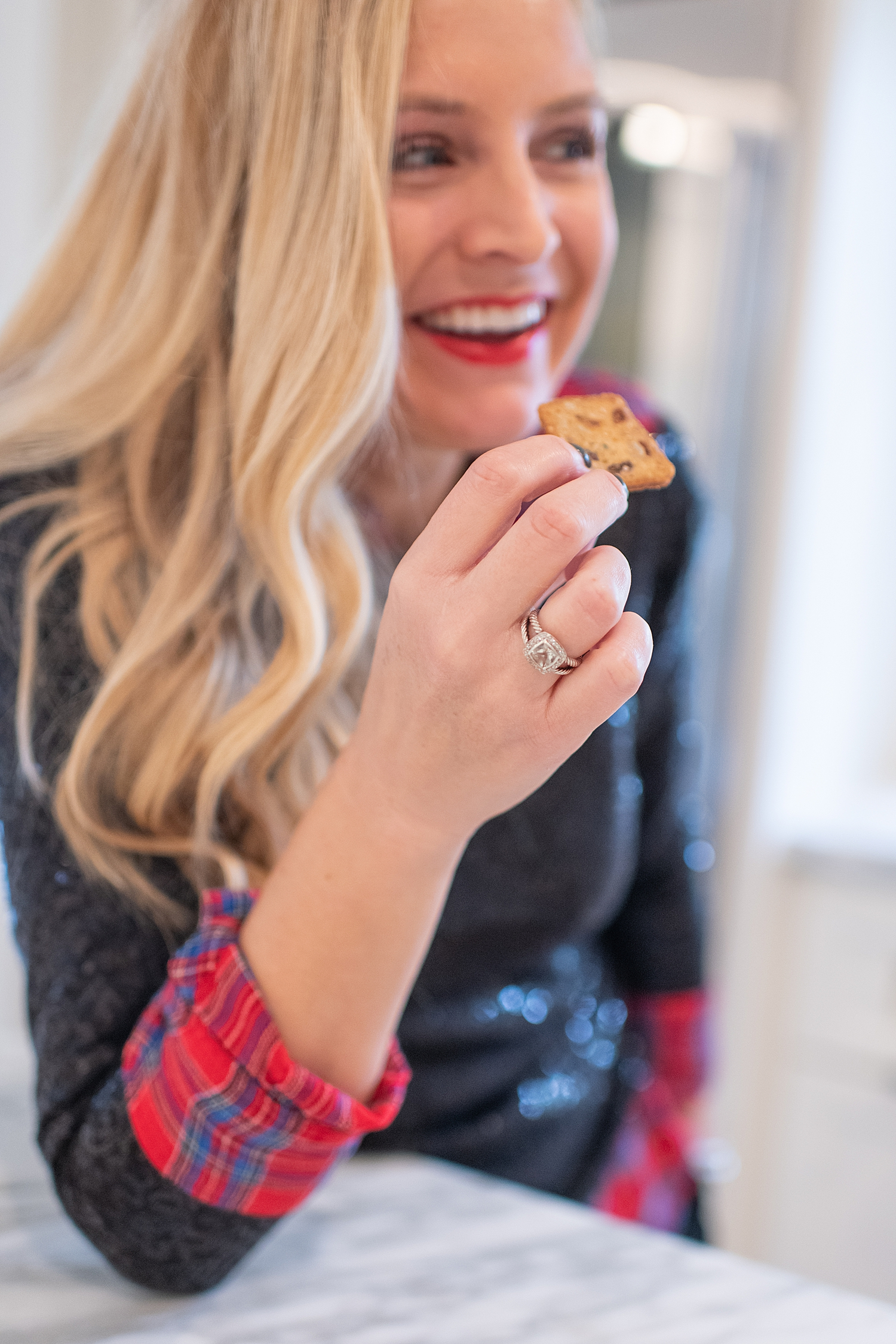 Top Houston life and style blogger, Fancy Ashley, features her tips to prepare the perfect Charcuterie Tray for the Holidays: image of a woman holding eating a cracker