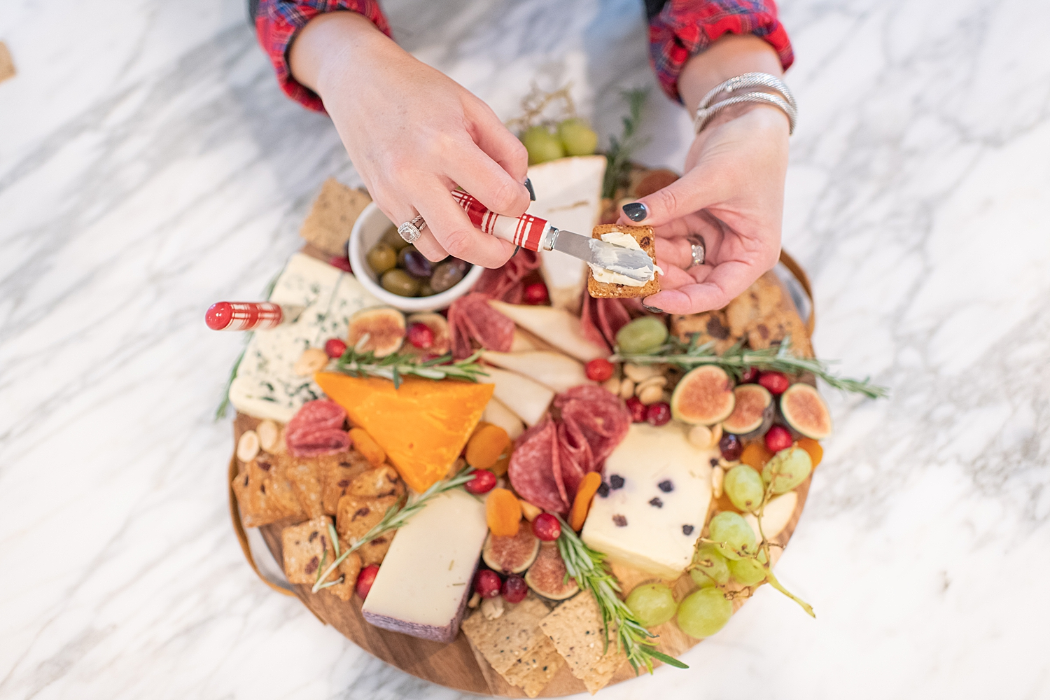 Top Houston life and style blogger, Fancy Ashley, features her tips to prepare the perfect Charcuterie Tray for the Holidays: image of a woman holding a festive charcuterie tray