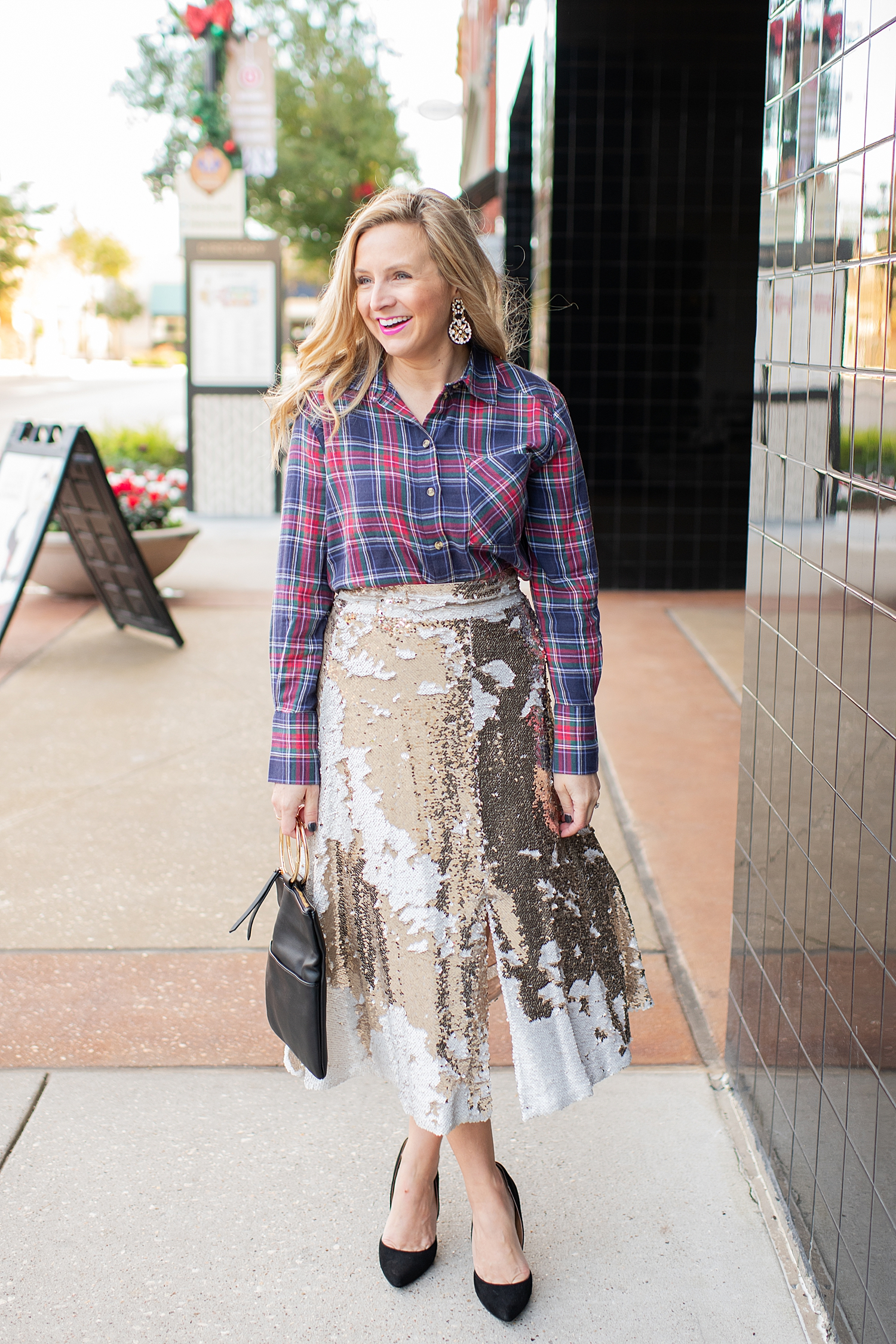 Top Houston fashion blogger, Fancy Ashley, features 7 Holiday Outfits perfect for the season: image of a woman wearing TOPSHOP plaid shirt, Eliza J sequin skirt, Kate Spade earrings, blck clutch all available at Nordstrom