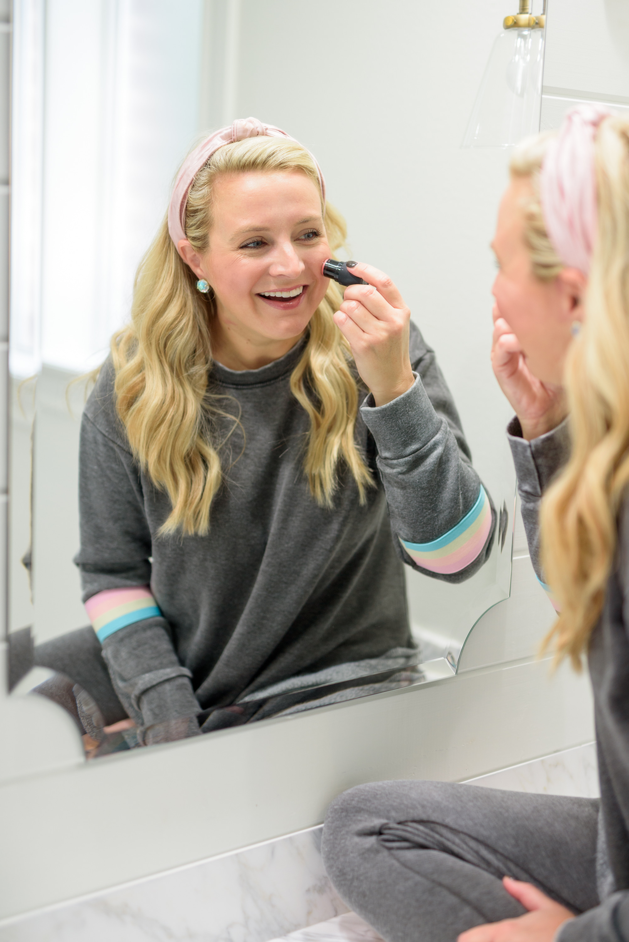 Fall Beauty by popular Houston beauty blog, Fancy Ashley: image of a woman sitting on her bathroom vanity and wearing a Burnout Stripe Sweatshirt VINTAGE HAVANA and Burnout Stripe Joggers VINTAGE HAVANA and using a blush stick.