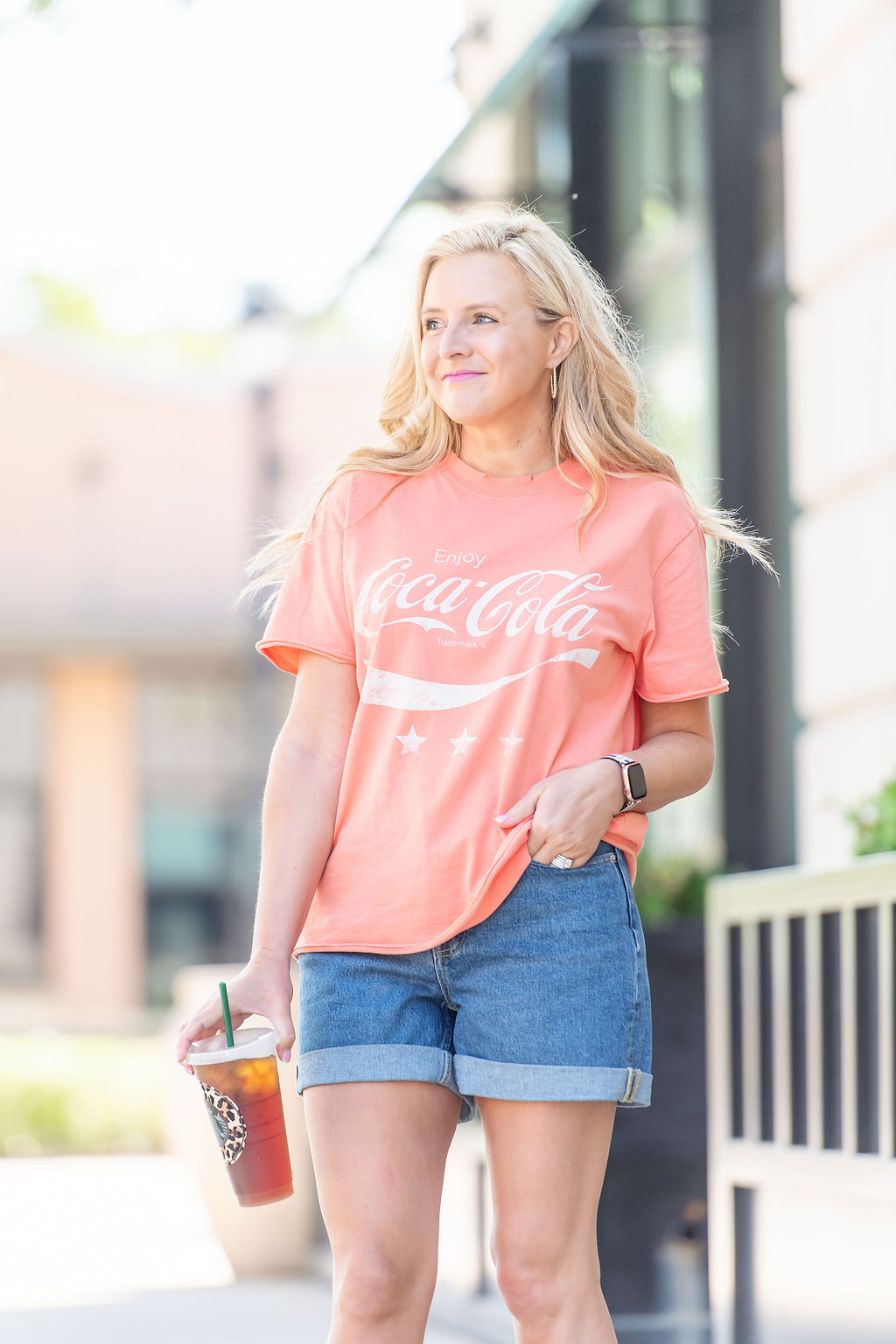 Denim Shorts by popular Houston fashion blog, The House of Fancy: image of a woman standing outside and wearing a Cocoa Cola t-shirt with a pair of denim shorts and studded gold strap sandals.