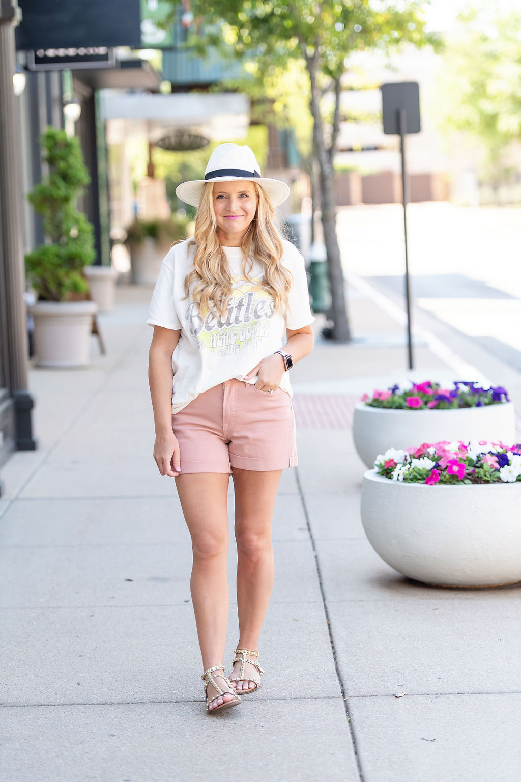 Denim Shorts by popular Houston fashion blog, The House of Fancy: image of a woman standing outside and wearing a The Beatles graphic t-shirt, pink denim shorts, white fedora hat, and studded gold strap sandals.