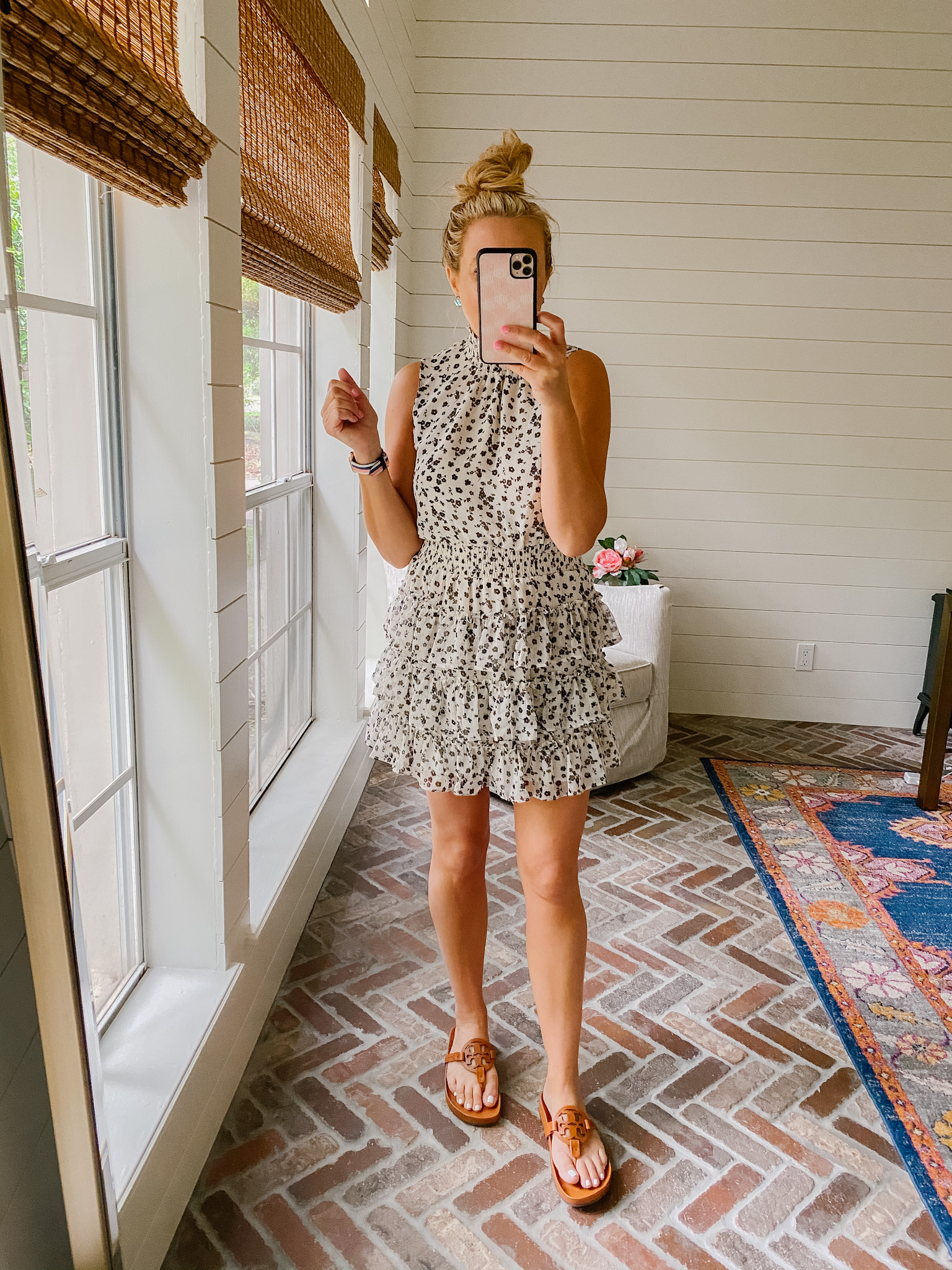 Express New Arrivals by popular Houston fashion blog, The House of Fancy: image of a woman wearing a Express sleeveless black and tan floral print ruffle tiered dress and brown slide sandals.