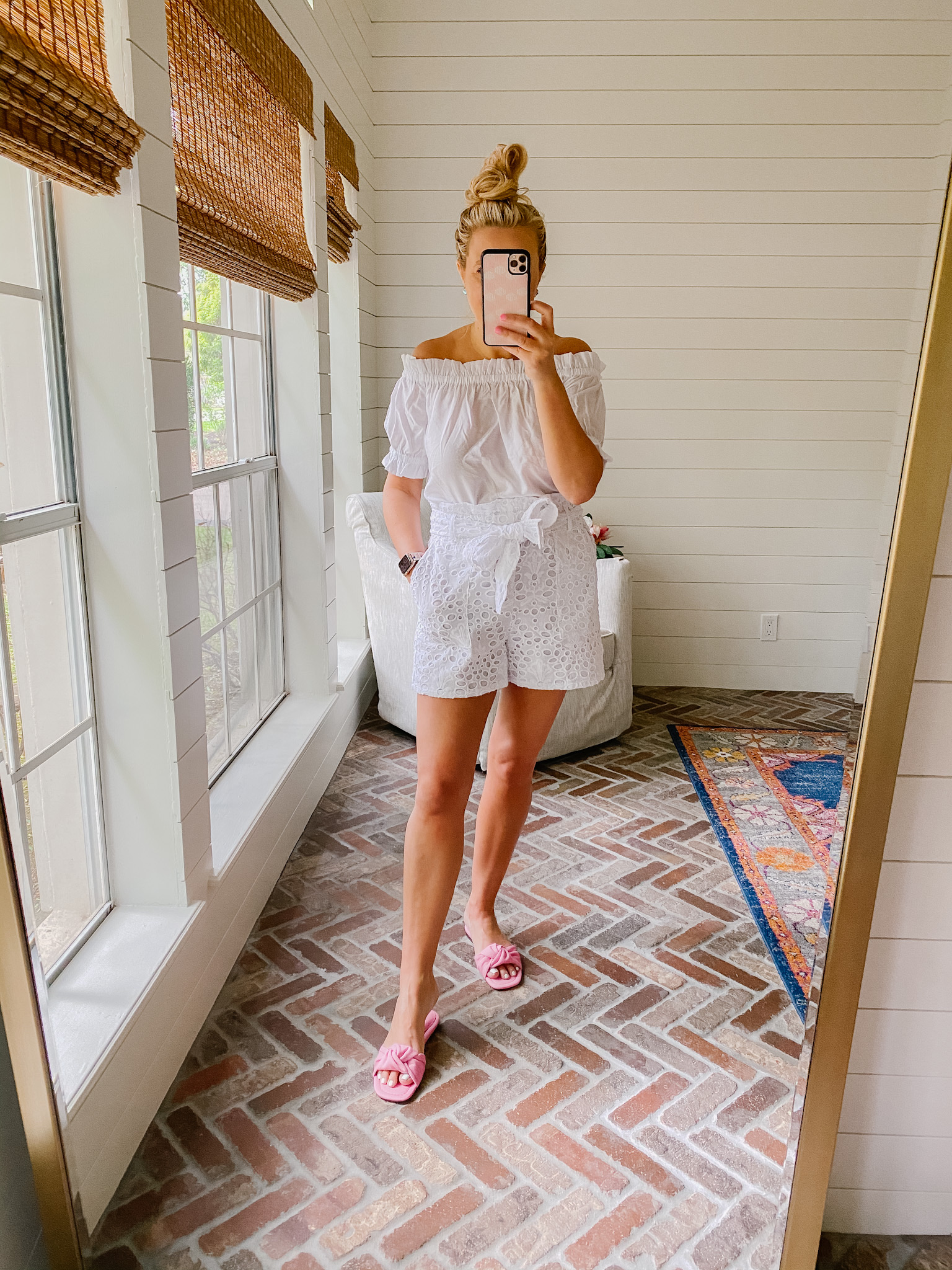 Express New Arrivals by popular Houston fashion blog, The House of Fancy: image of a woman wearing a Express white off the shoulder top with white eyelet paper bag shorts and pink slide sandals.