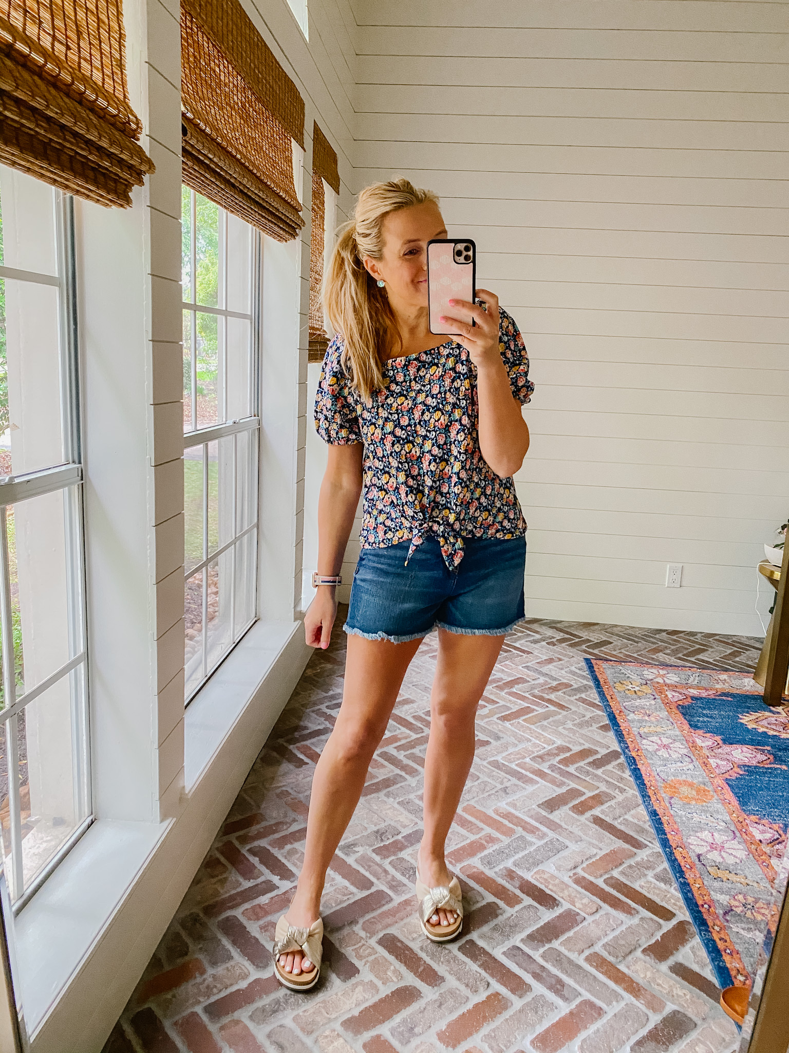 Loft Clothing by popular Houston fashion blog, The House of Fancy: image of a woman wearing a Loft floral print tie front top with distressed hem denim shorts and metallic slide sandals.