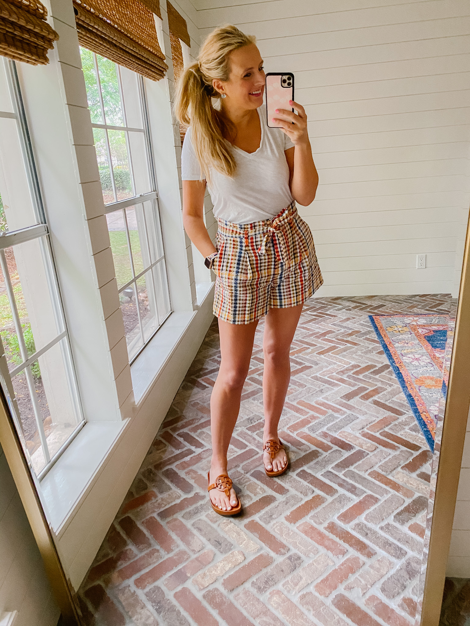 Loft Clothing by popular Houston fashion blog, The House of Fancy: image of a woman wearing a Loft white v-neck tee shirt, plaid paper bag shorts with brown Tory Burch slide sandals.