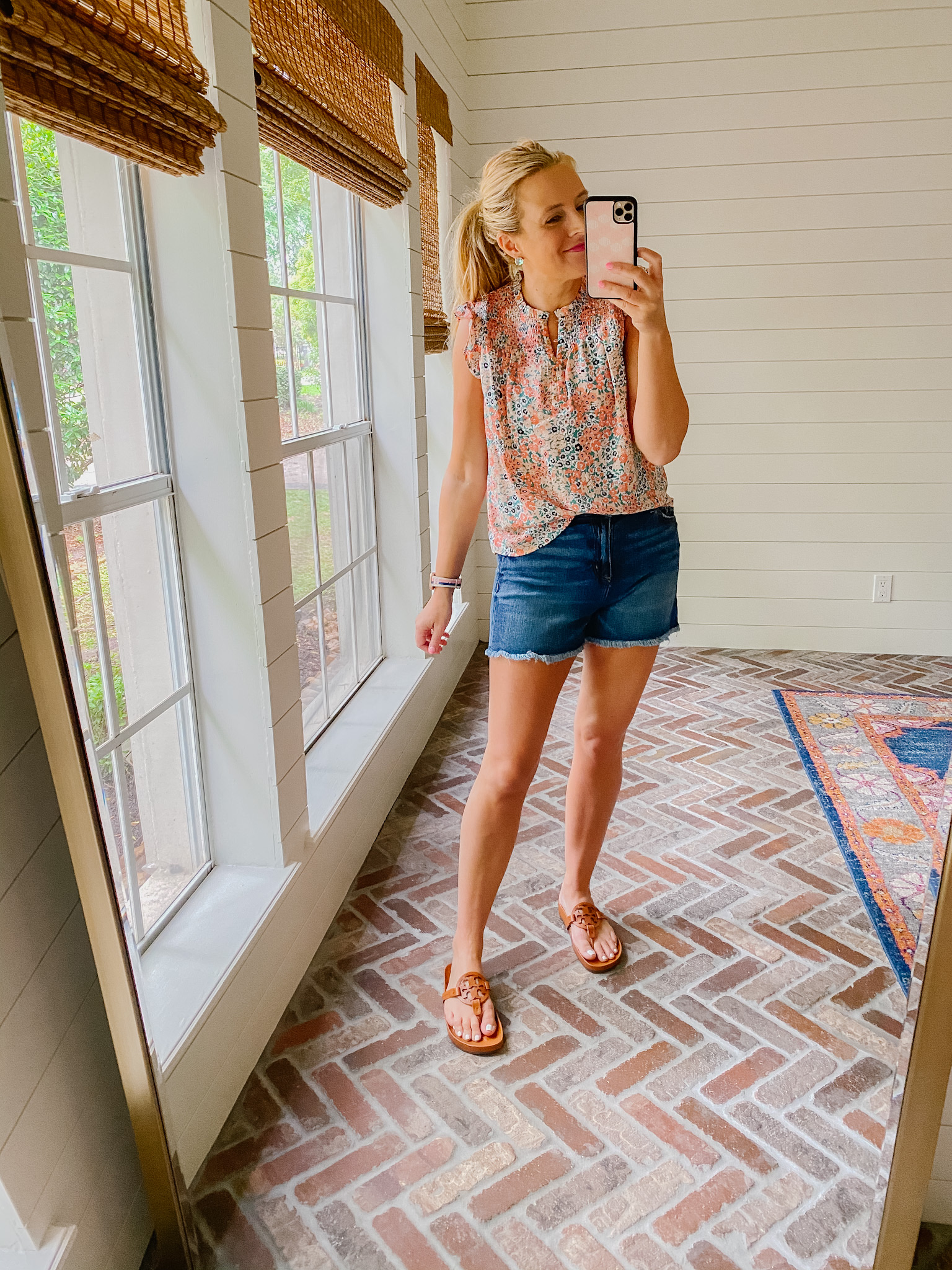 Loft Clothing by popular Houston fashion blog, The House of Fancy: image of a woman wearing a Loft floral print flutter sleeve top, distressed hem denim shorts, and brown Tory Burch slide sandals.