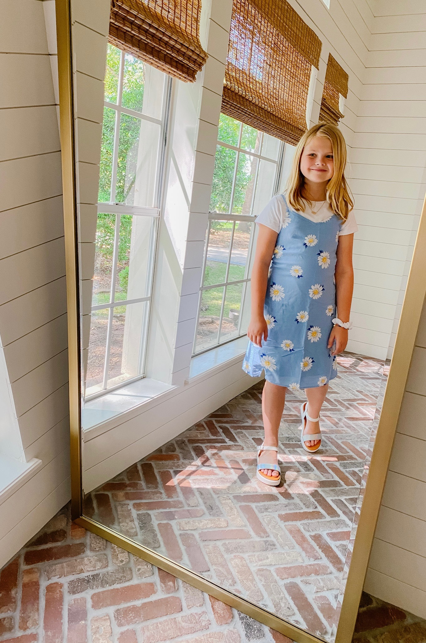 Spring Clothing by popular Houston fashion blog, The House of Fancy: image of a girl wearing a blue and white floral print dress, white t-shirt and metallic sandals.
