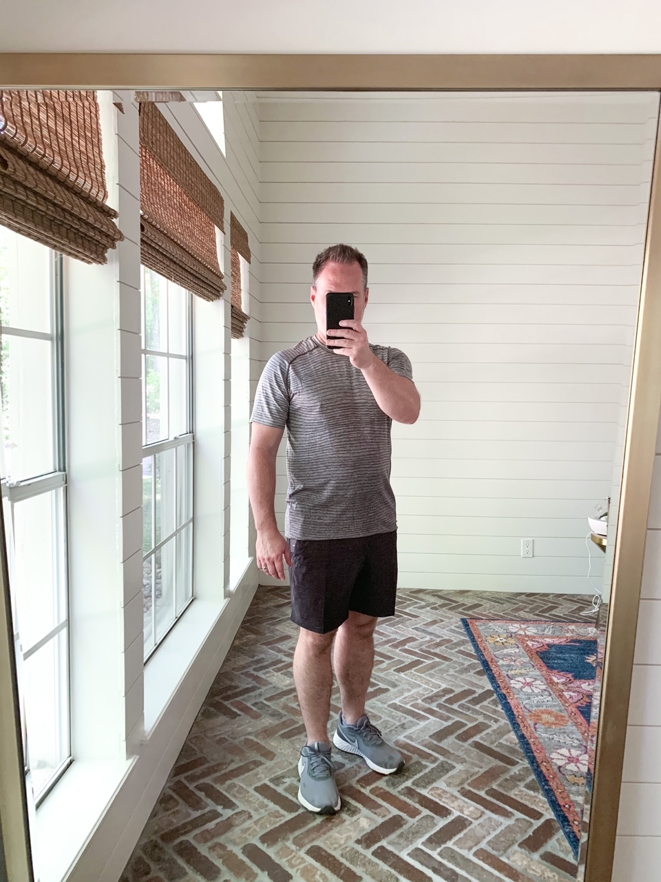 Men's Workout Gear by popular Houston fashion blog, The House of Fancy: image of a man wearing a Lululemon stripe shirt, Lululemon shorts and grey athletic shoes.