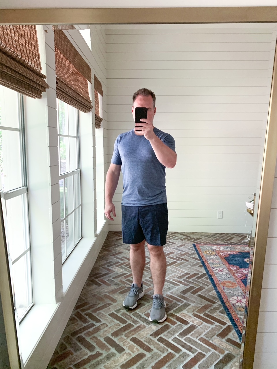 Men's Workout Gear by popular Houston fashion blog, The House of Fancy: image of a man wearing a Lululemon blue shirt, Lululemon shorts, and grey athletic shoes.