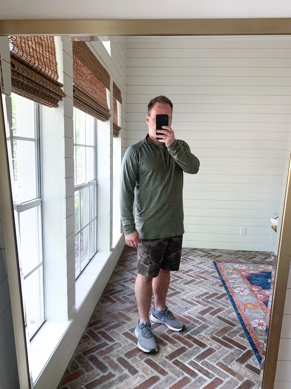 Men's Workout Gear by popular Houston fashion blog, The House of Fancy: image of a man wearing a Lululemon long sleeve pullover, Lululemon shorts, and grey athletic shoes.