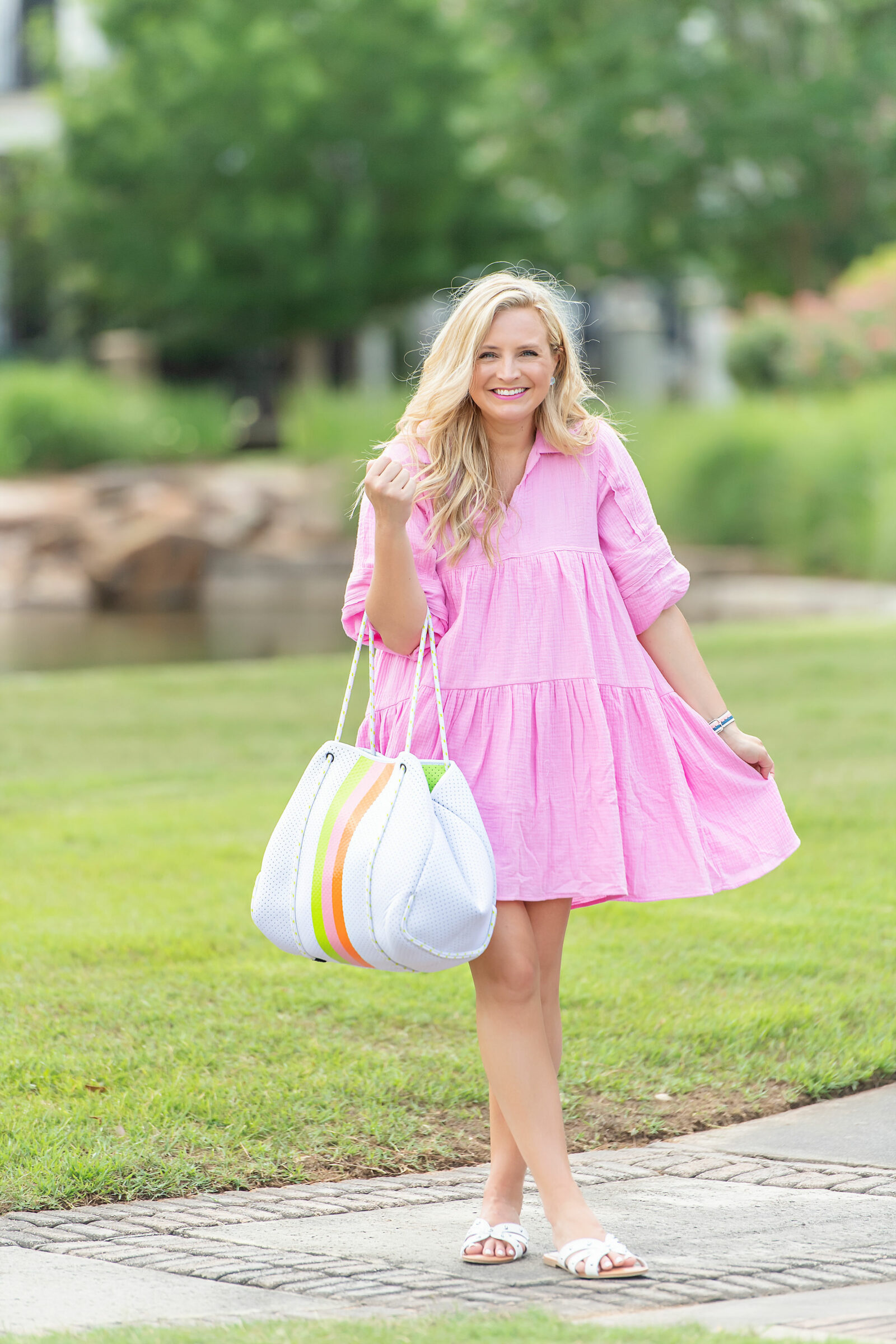Social Threads Summer Handbag by popular Houston fashion blog, The House of Fancy: image of a woman standing outside and wearing a pink babydoll dress and hold a white Social Threads Summer Handbag with green, pink, and orange stripes.
