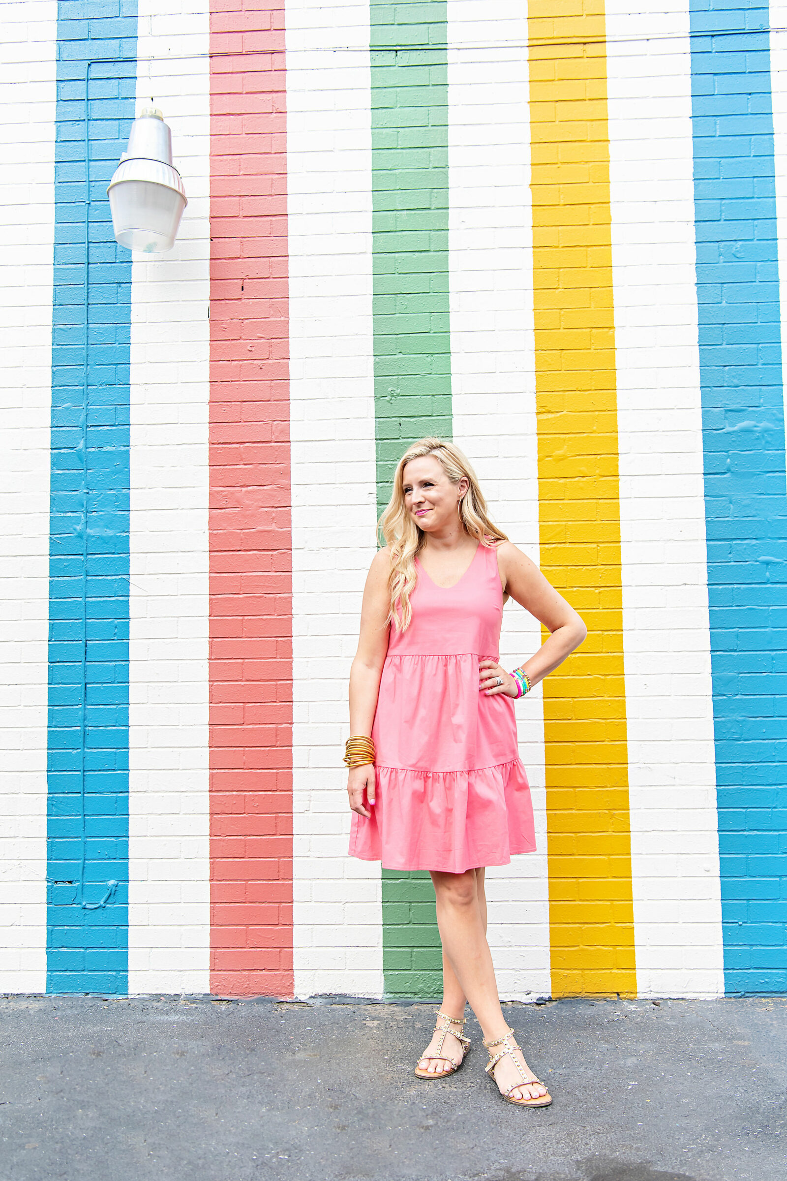 pink graduation dress |. pink graduation dress | Graduation Dress by popular Houston fashion blog, The House of Fancy: image of a woman standing in front of a multi color strip mural and wearing a Gibsonlook Ashley tiered poplin dress, studded gold strap sandals, gold bracelets and colorful stretch bracelets.
