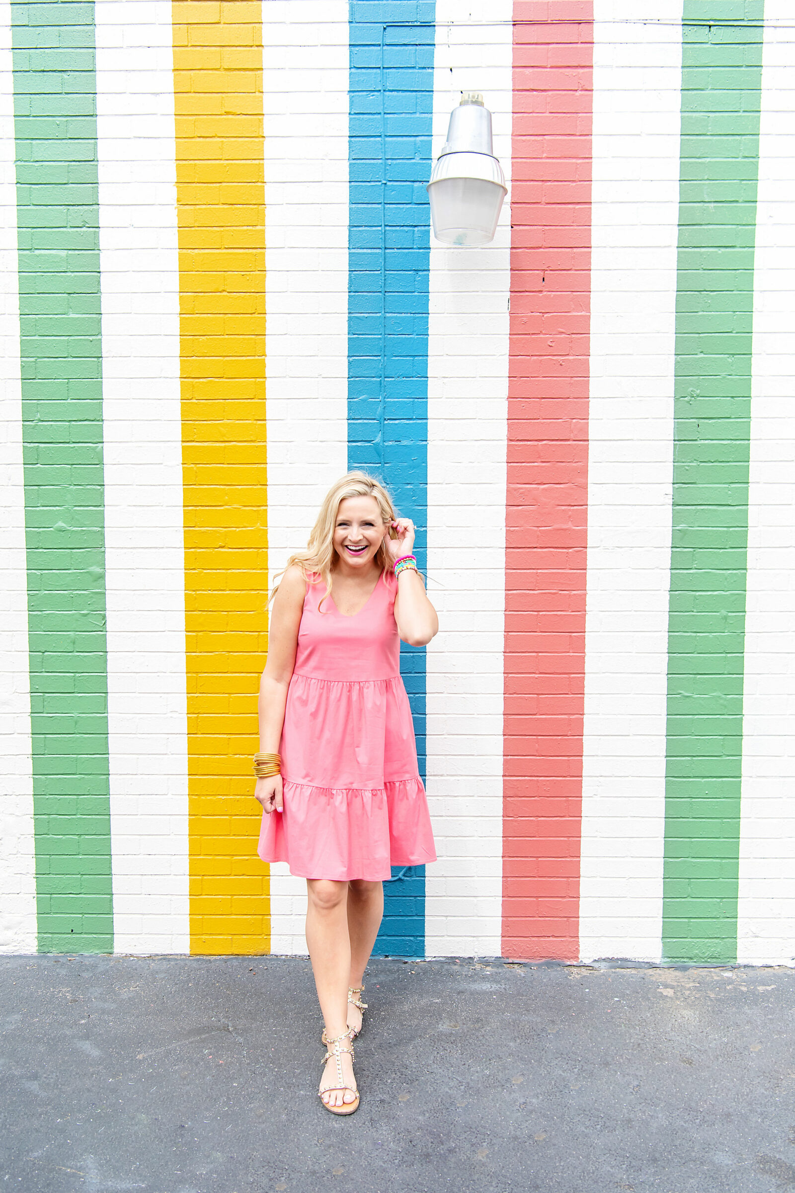 pink graduation dress | Graduation Dress by popular Houston fashion blog, The House of Fancy: image of a woman standing in front of a multi color strip mural and wearing a Gibsonlook Ashley tiered poplin dress, studded gold strap sandals, gold bracelets and colorful stretch bracelets.