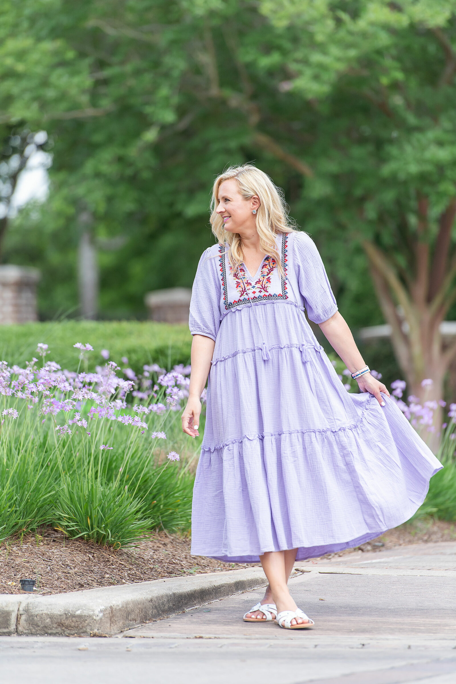 Prettiest Embroidered Dresses for Summer   Embroidered Dresses by popular Houston fashion blog, The House of Fancy: image of a woman standing by some purple flowers and wearing a floral embroidered purple tiered maxi dress.