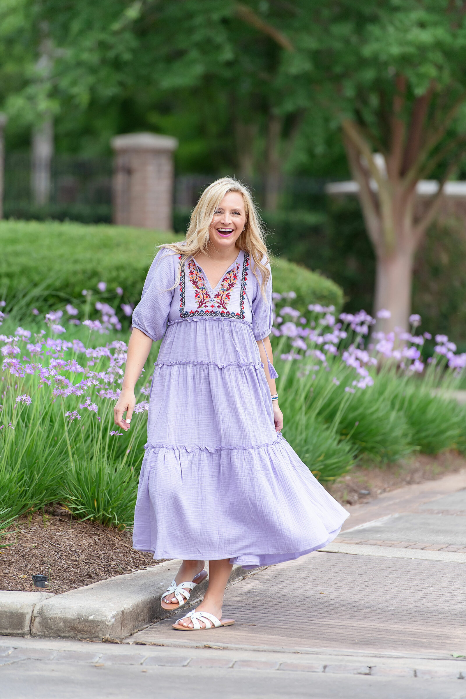 Best Sellers by popular Houston fashion blog, The House of Fancy: image of a woman standing outside by some purple flowers and wearing a floral embroidered purple tiered maxi dress.