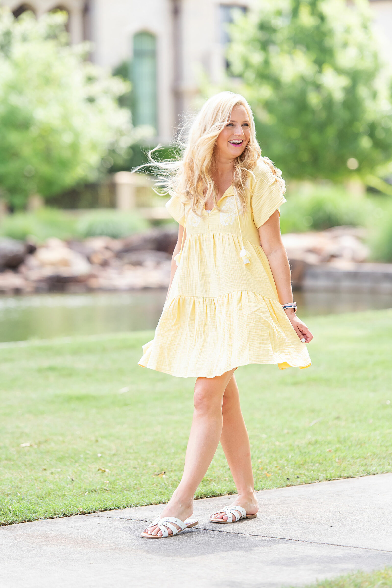 The Prettiest Embroidered Dresses for Summer  . Prettiest Embroidered Dresses for Summer   Embroidered Dresses by popular Houston fashion blog, The House of Fancy: image of a woman walking outside on a sidewalk and wearing a yellow embroidered dress with white strap slide sandals.