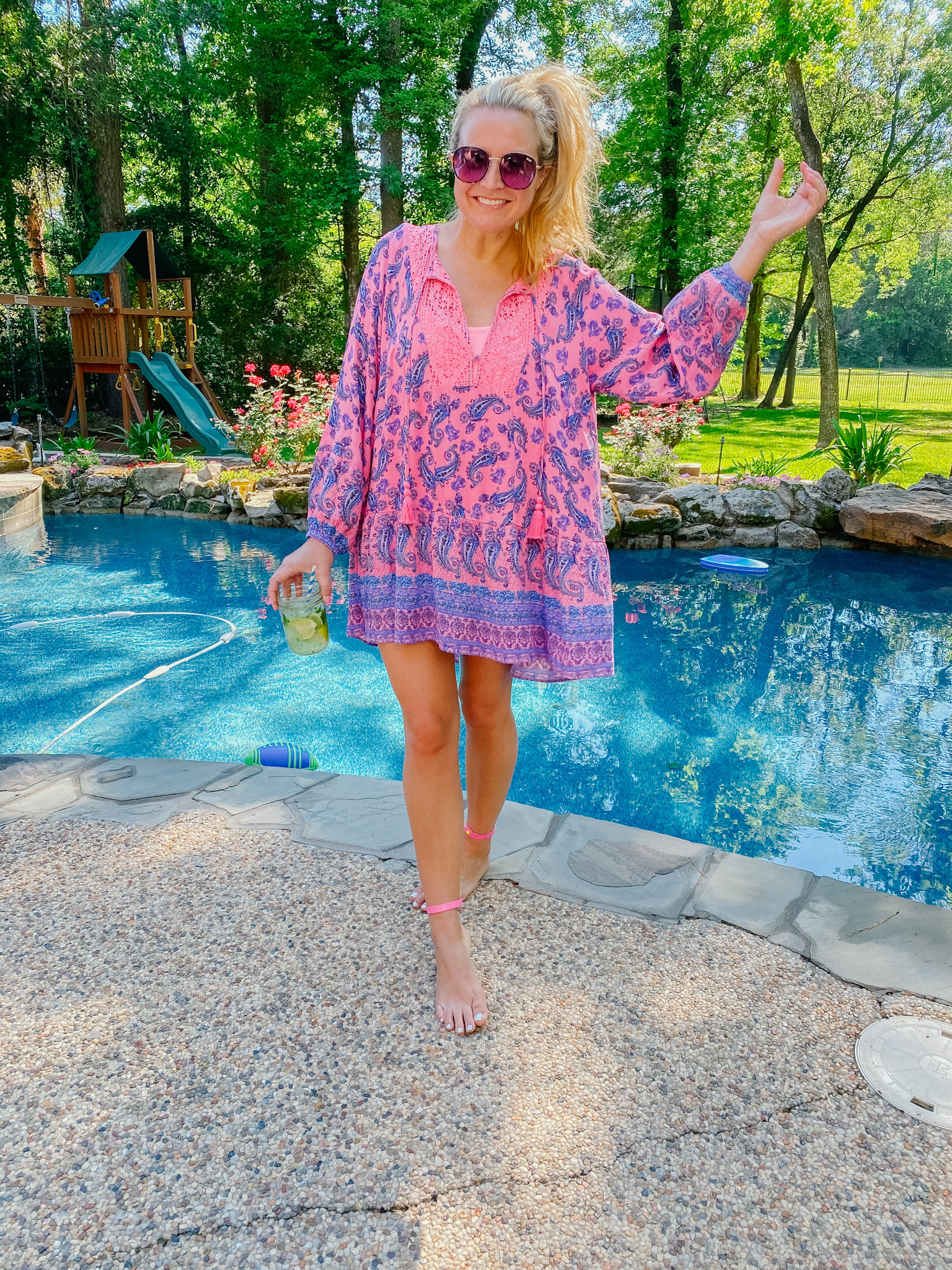 Best Sellers by popular Houston fashion blog, The House of Fancy: image of a woman standing next to a swimming pool and wearing a pink and blue paisley print dress with some oversized sunglasses.
