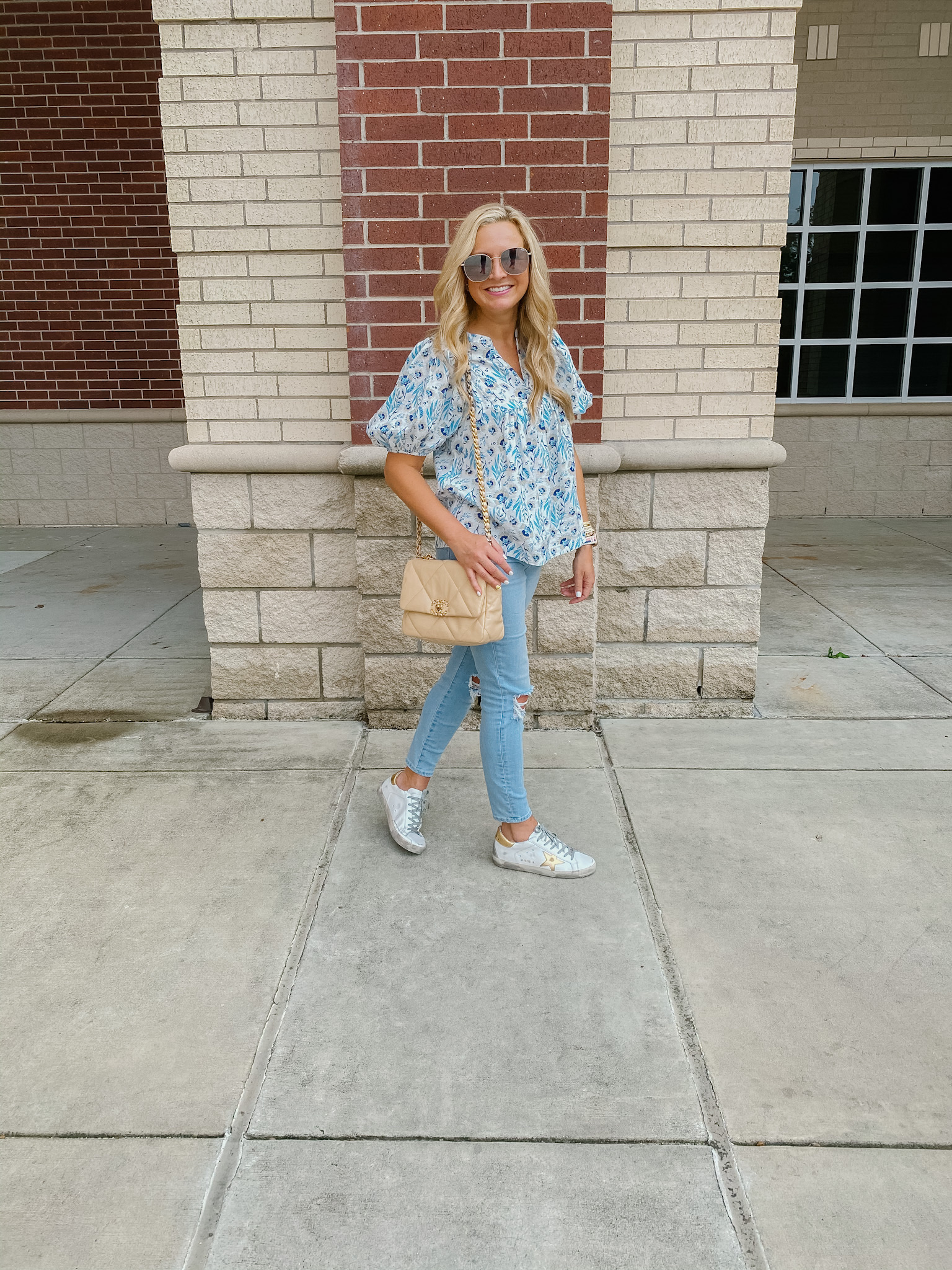 Best Sellers by popular Houston fashion blog, The House of Fancy: image of a woman standing next to a brick building and wearing a blue floral print puff sleeve top, light wash distress denim and golden goose sneakers.