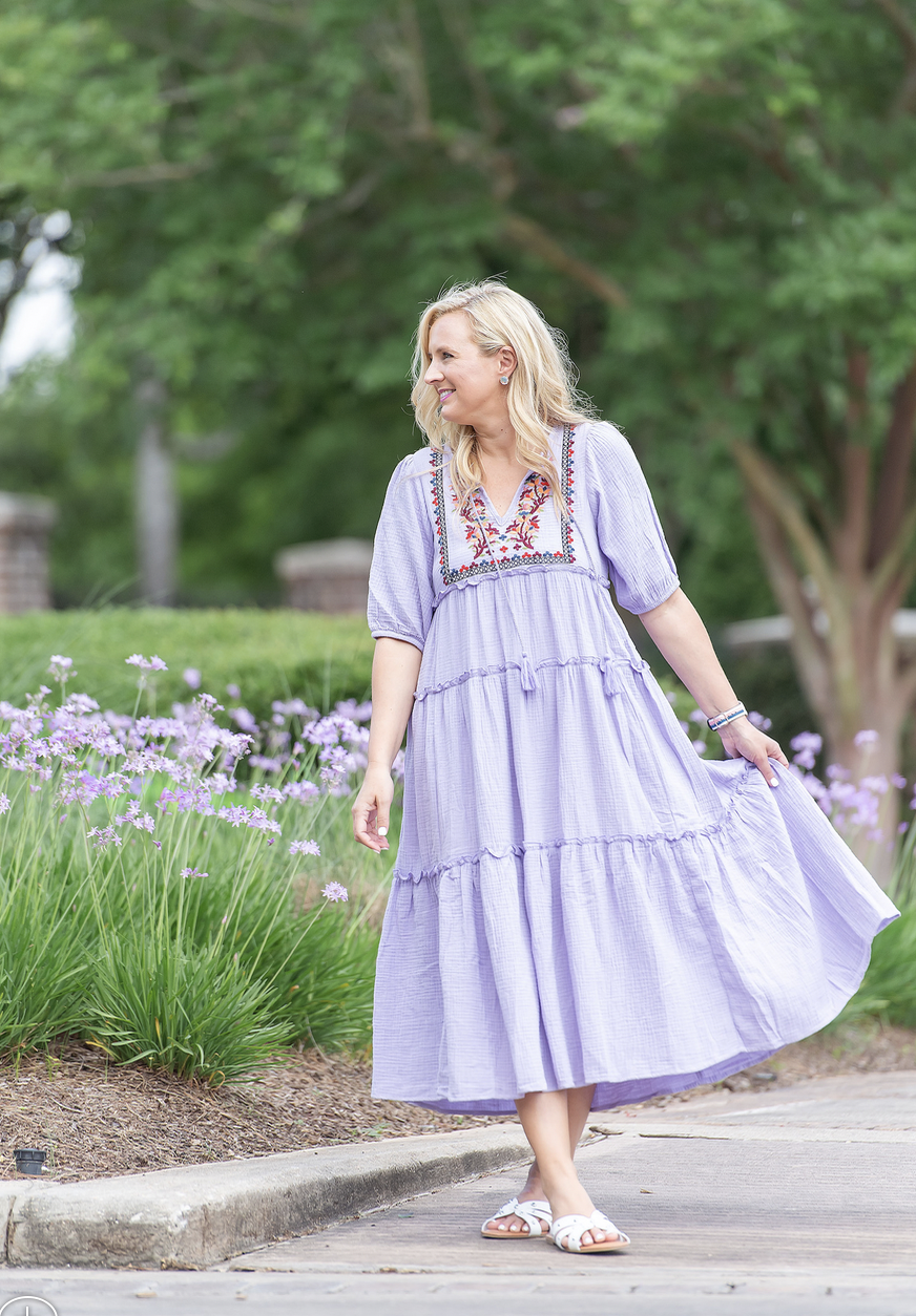 Best Sellers by popular Houston fashion blog, The House of Fancy: image of a woman standing by some purple flowers and wearing a purple floral embroidered tiered maxi dress with white strap slide sandals.