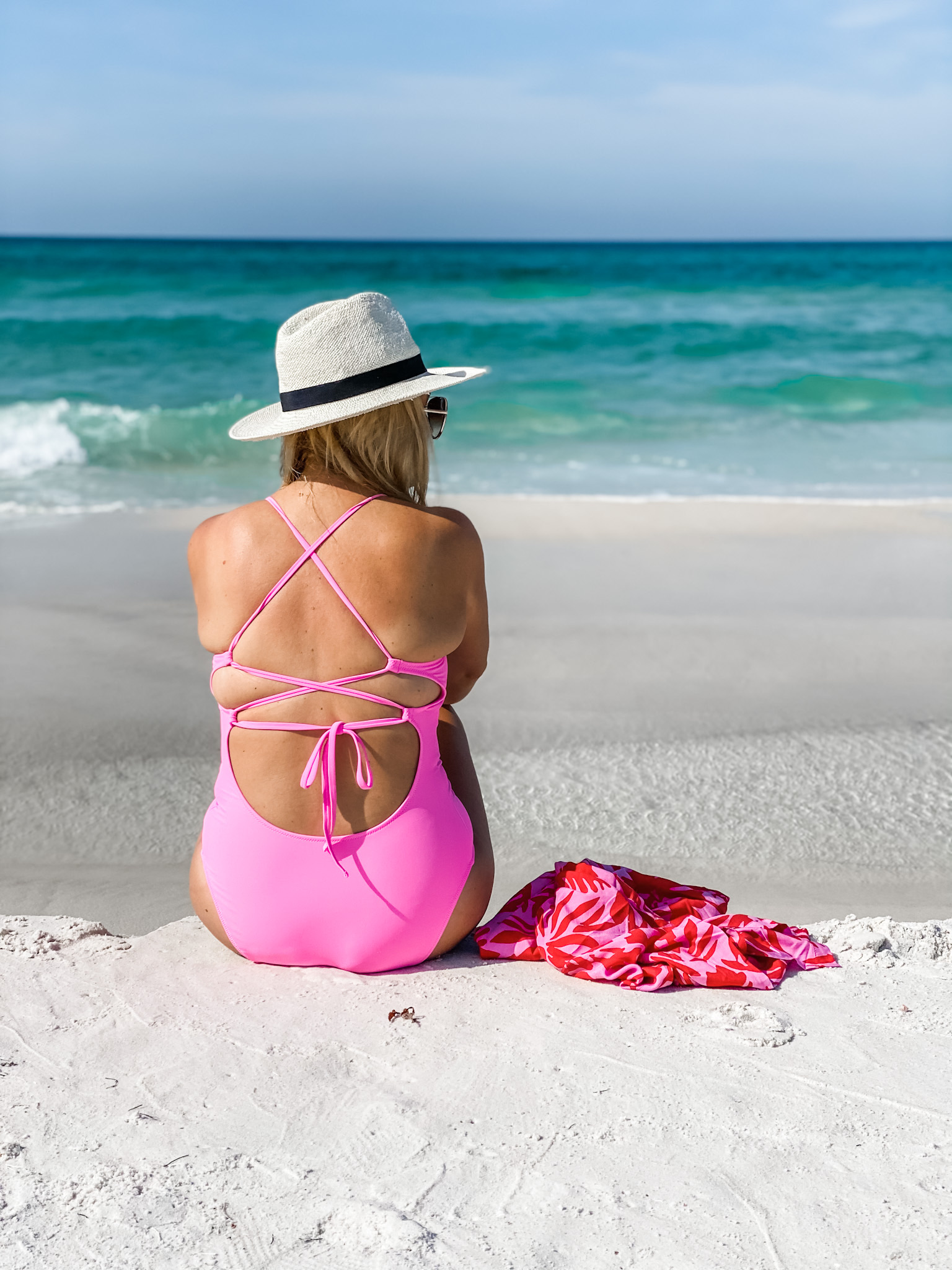 swim packed for my beach vacation | Beach Vacation by popular Houston fashion blog, The House of Fancy: image of a woman sitting on a white sand beach next to the ocean and wearing a pink one piece swimsuit and straw fedora.