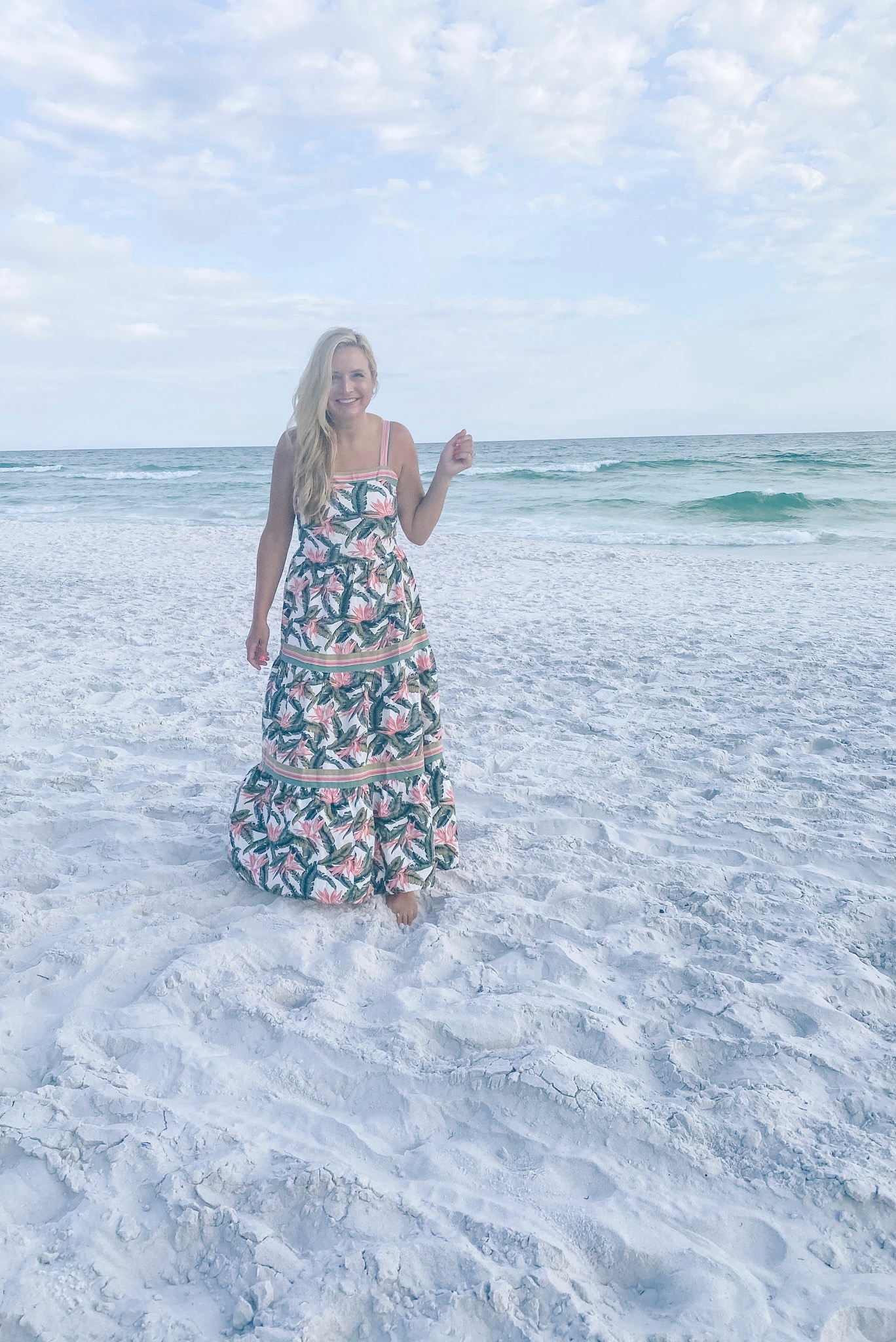 Summer Outfit Ideas by popular Houston fashion blog, The House of Fancy: image of a woman standing on a white sand beach and wearing a pink floral print maxi dress.