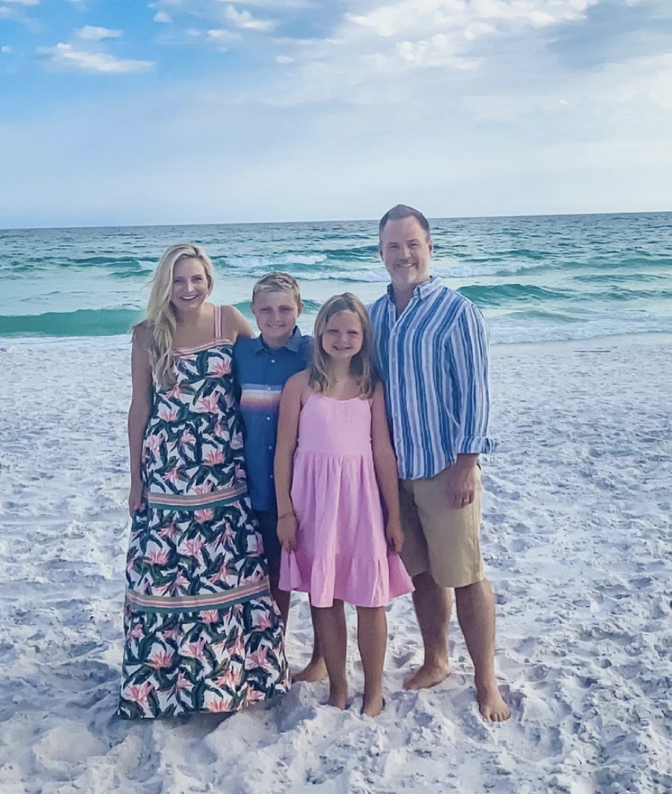 fancy Ashley family photo looks   Family Photo Outfits by popular Houston fashion blog, The House of Fancy: image of a family standing on a white sand beach and wearing a pink floral print maxi dress, pink tiered dress, blue stripe button up shirt, tan shorts, and blue button shirt with a multi color stripe accent.